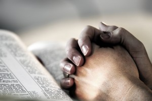 bigstockphoto_Prayinghandsbible_283463-300x200